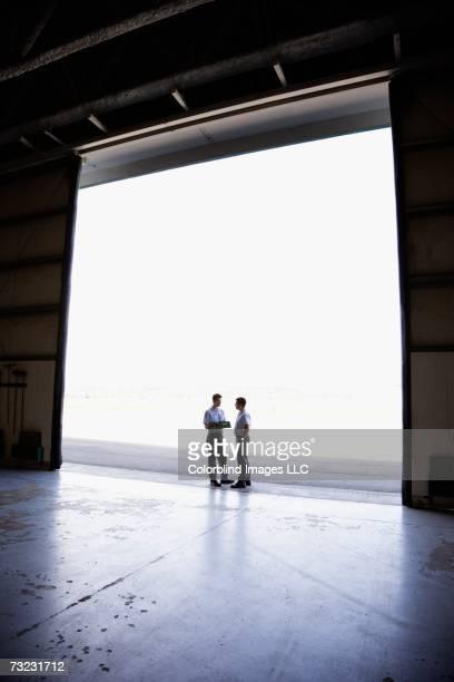 Two male workers in hangar doorway