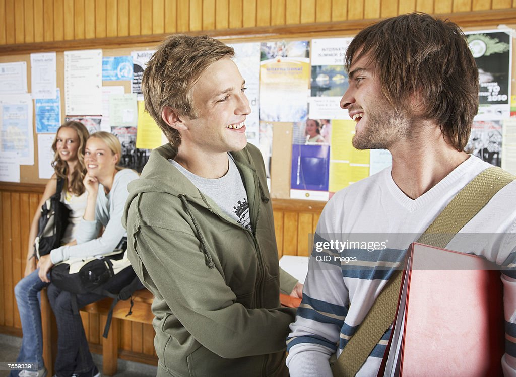 Two males by a bulletin board with two females in background : Stock Photo