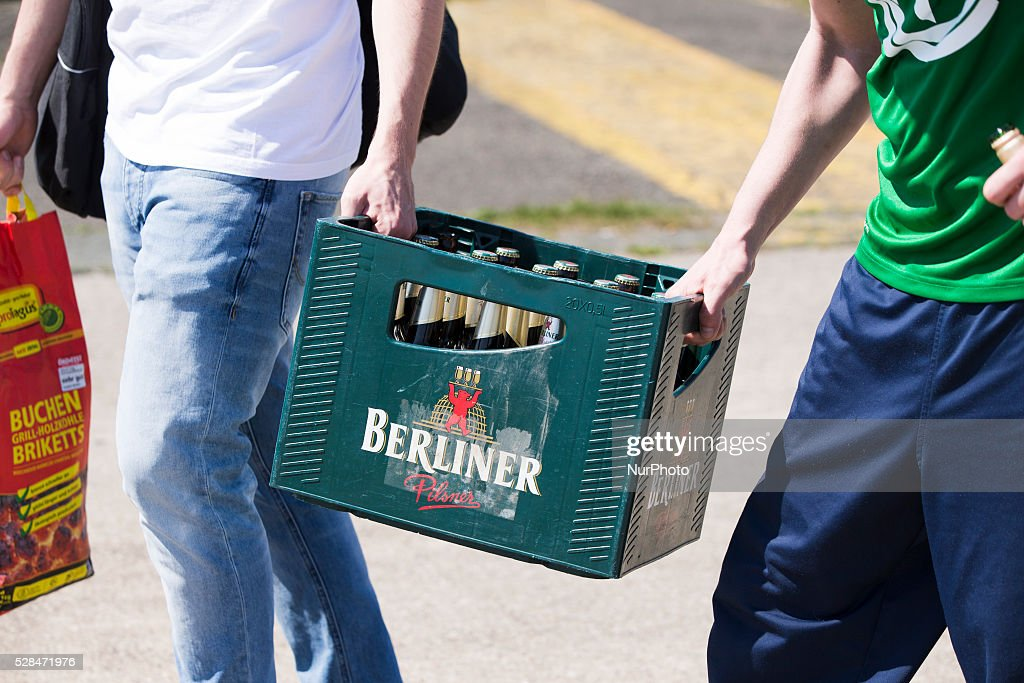 Two man carry a box of beer of the label 'Berliner Pilsner' in the Tempelhofer Feld park during Father's Day or Man's Day in Berlin, Germany on May 5, 2016. In Germany is tradition for groups of males to do a hiking tour and use the holiday as occasion to get drunk.