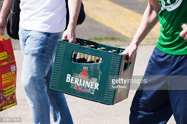 Two man carry a box of beer of the label 'Berliner Pilsner' in the Tempelhofer Feld park during Father's Day or Man's Day in Berlin Germany on May 5...