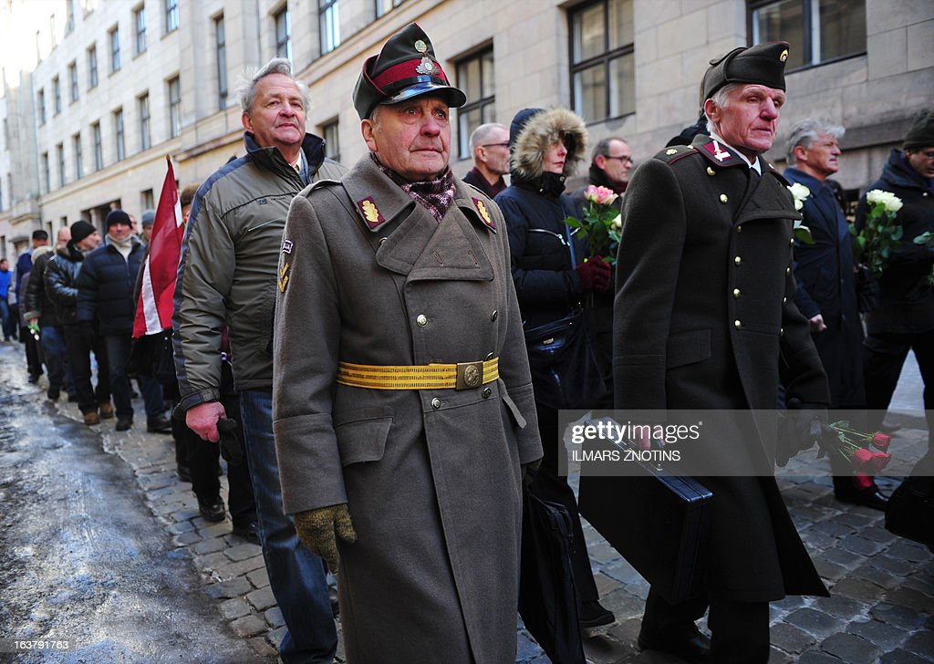 Two man dressed in pre-WWII Latvian military uniforms walk along with veterans of the Latvian Legion, a force that was commanded by the German Nazi Waffen SS, and their sympathizers to the Monument of Freedom in Riga, Latvia on March 16, 2013 to commemorate a key 1944 battle in their ultimately failed attempt to stem a Soviet advance. Jewish groups, Moscow and some in Latvia's ethnic-Russian community see the parade as glorifying Nazism because the Legion, founded in 1943, was commanded by Germany's Waffen SS.AFP PHOTO / ILMARS ZNOTINS