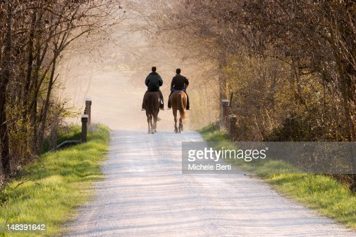 Two man riding horses in dirt road at sunset