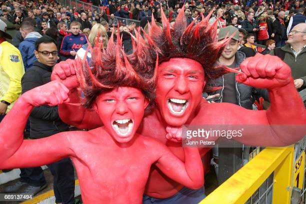 Two Manchester United fans watch from the stand during the Premier League match between Manchester United and Chelsea at Old Trafford on April 16...