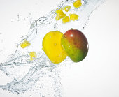 Two mango halves being splashed with water
