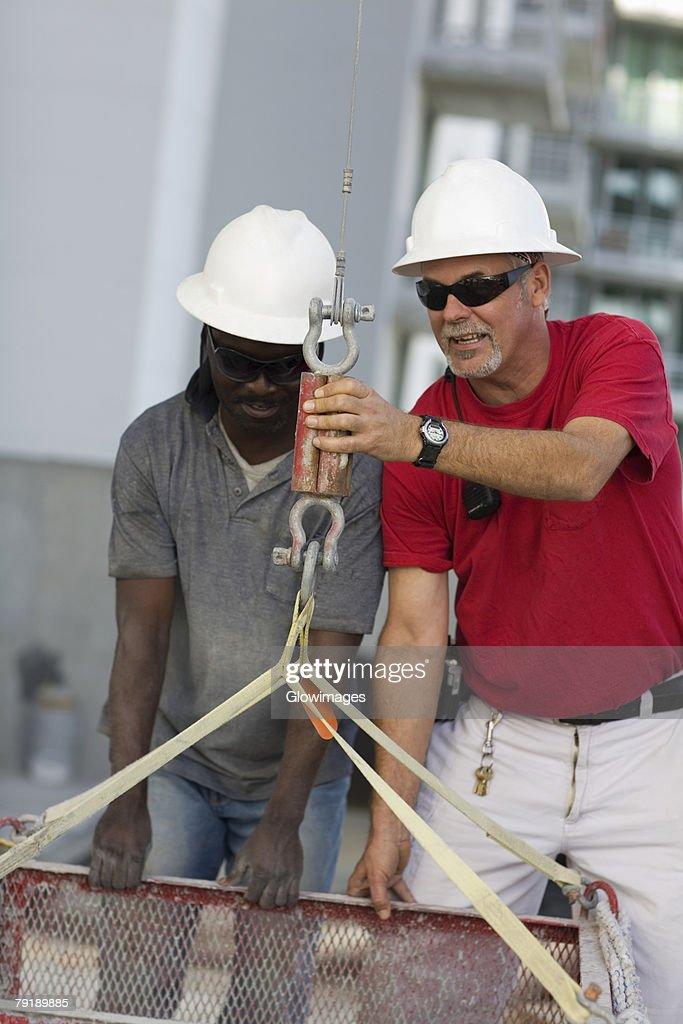 Two manual workers fastening a container in the hook of a lift : Stock Photo