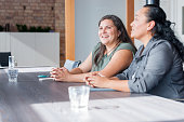 Two Maori women on one side of table in involved in discussion during business meeting