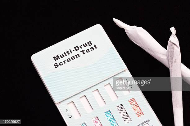 Two marijuana joints next to a multi-drug home test kit