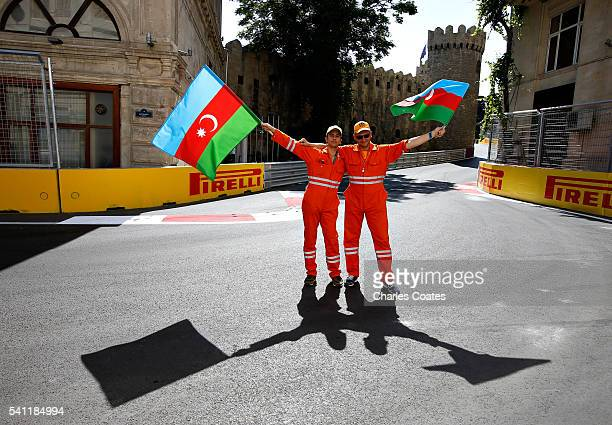 Two marshals waves the Azerbaijan flag on track before the European Formula One Grand Prix at Baku City Circuit on June 19 2016 in Baku Azerbaijan