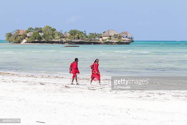 Two Masai warriors walking on the beach