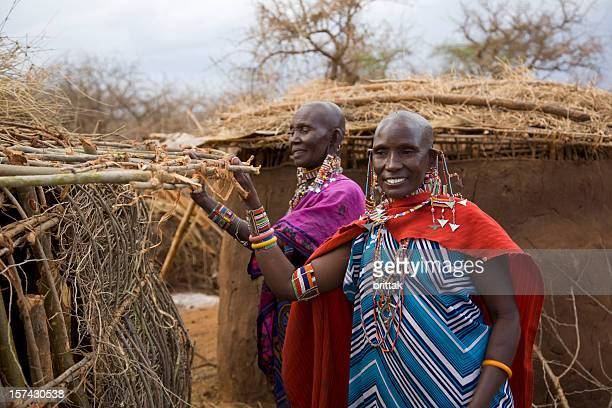 Two masai woman preparing the roof of their mud house.