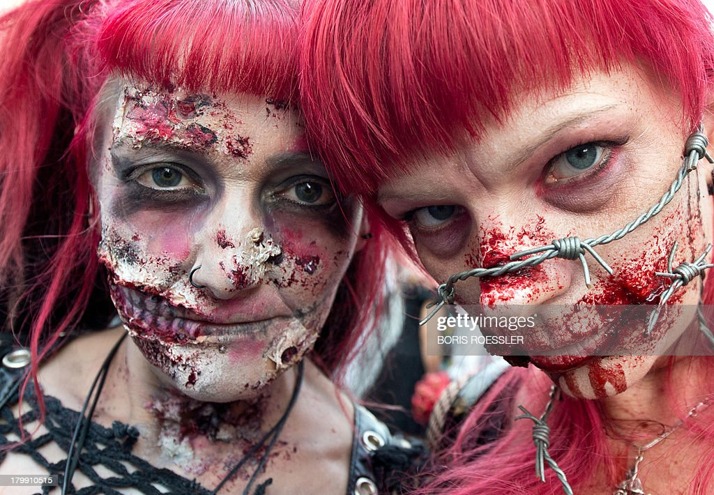 Two masked participants pose for a photographer during a zombie walk event in Frankfurt am Main, central Germany, on September 7, 2013.