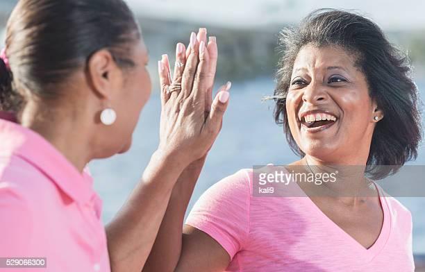 Due matura donna afroamericana in rosa, alta cinque