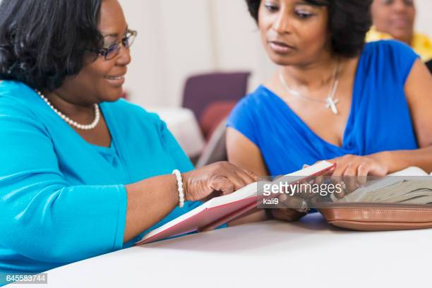 Two mature black women reading and discussing the bible
