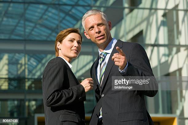 two mature business people having conversation in front of office building