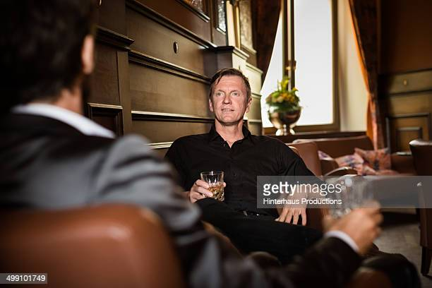 Two mature businessman having whiskey in a bar