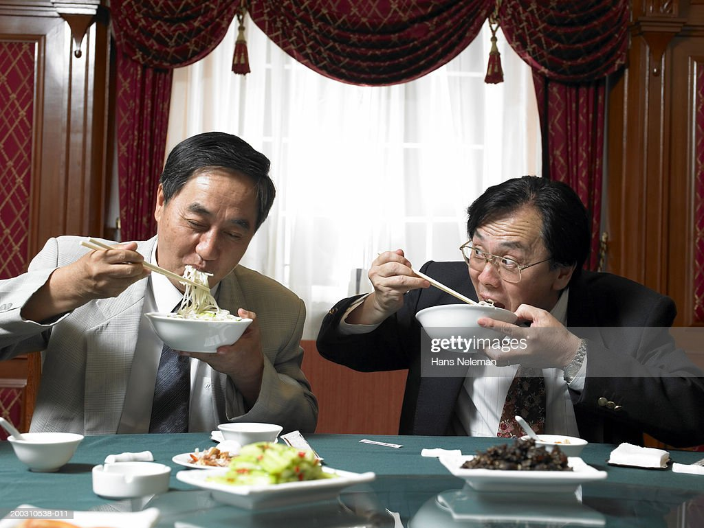 Two mature businessmen eating noodles at banquet table