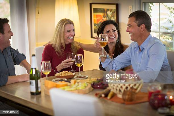 Two mature couples drinking wine and chatting at dinner party