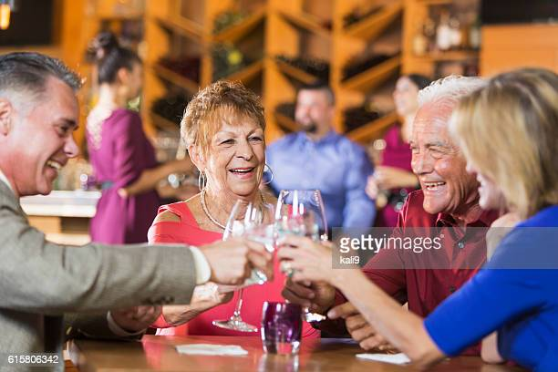 Two mature couples having drinks at restaurant