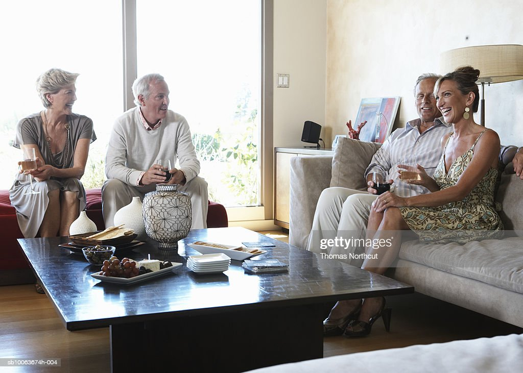 Two mature couples relaxing in living room having drinks, smiling : Stock Photo
