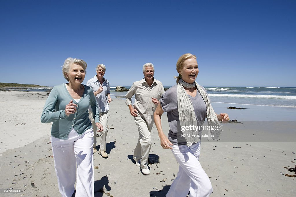 Two mature couples running on beach : Stock Photo