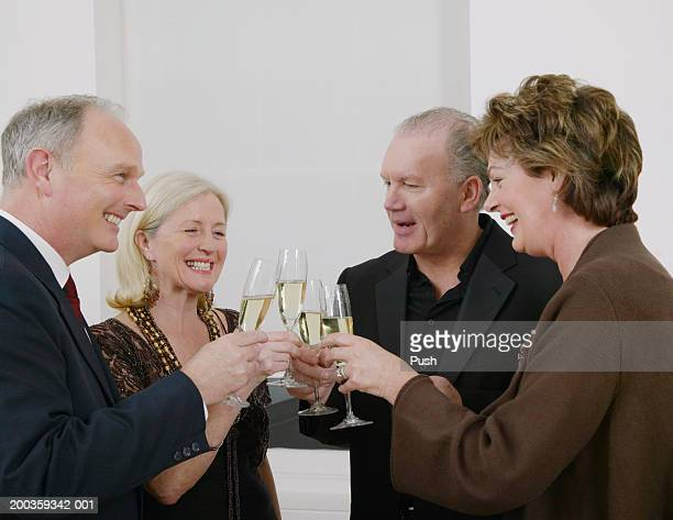 Two mature couples toasting each other with white wine, smiling
