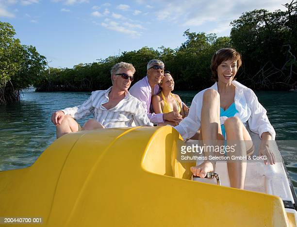 Two mature couples using pedalo, smiling