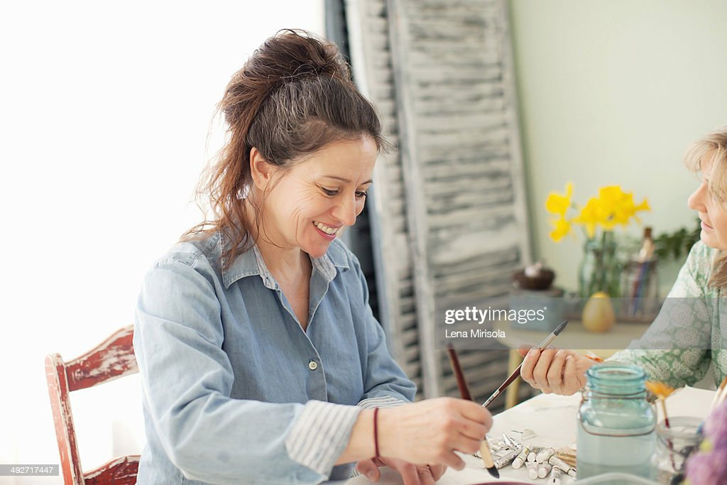 Two mature female artists painting watercolour in studio : Stock Photo
