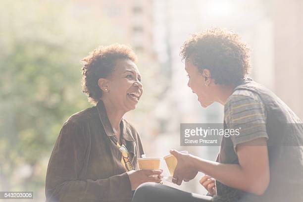 Two mature female friends chatting on street