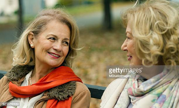 Two mature friends talking at the park.