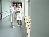 Two mature male doctors talking in hospital corridor