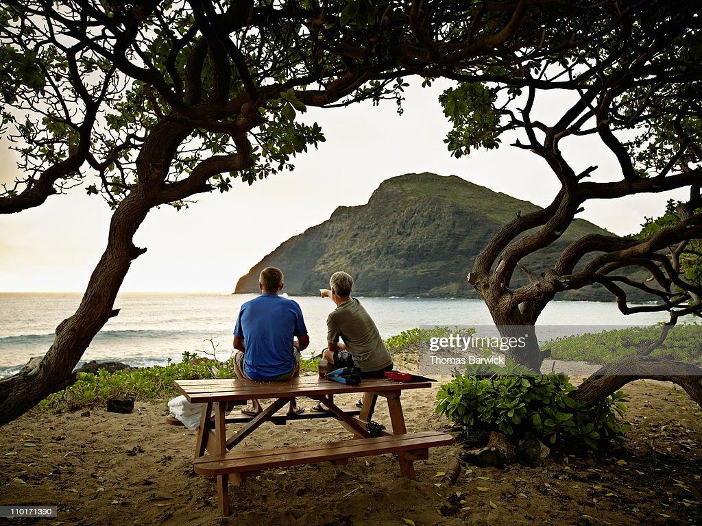 Two mature male friends sitting watching sunrise : Stock Photo