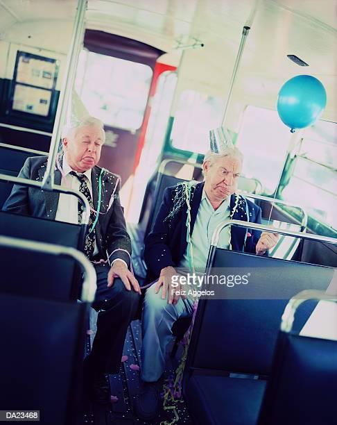 Two mature men covered in party streamers pulling faces on bus