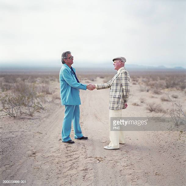 Two mature men in suits shaking hands in the desert