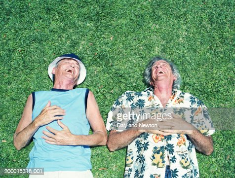 Two mature men lying on grass, laughing, overhead view : Bildbanksbilder