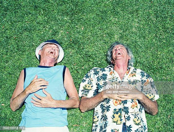 Two mature men lying on grass, laughing, overhead view