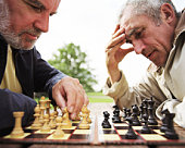 Two mature men playing chess on picnic table in park, close-up