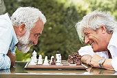 Two mature men playing chess, smiling, side view