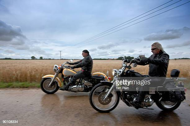 Two mature men riding motorcycles.