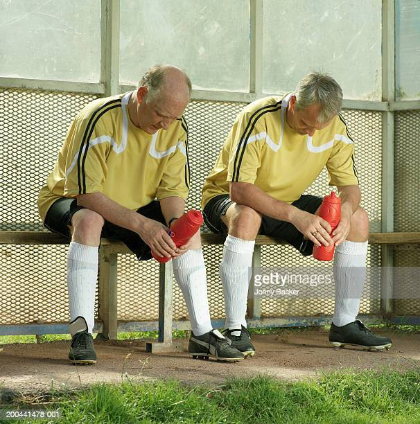 Two mature men sitting on substitute bench, holding water bottles