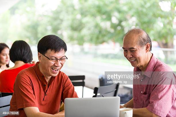 Two Mature Men Using Notebook at Outdoor Cafe