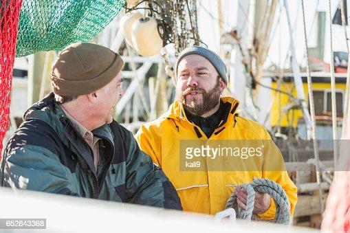 商業漁業のボートに取り組んでいる 2 つの成熟した男性 : ストックフォト
