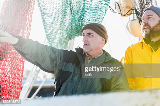 Two mature men working on commercial fishing boat : Stock-Foto