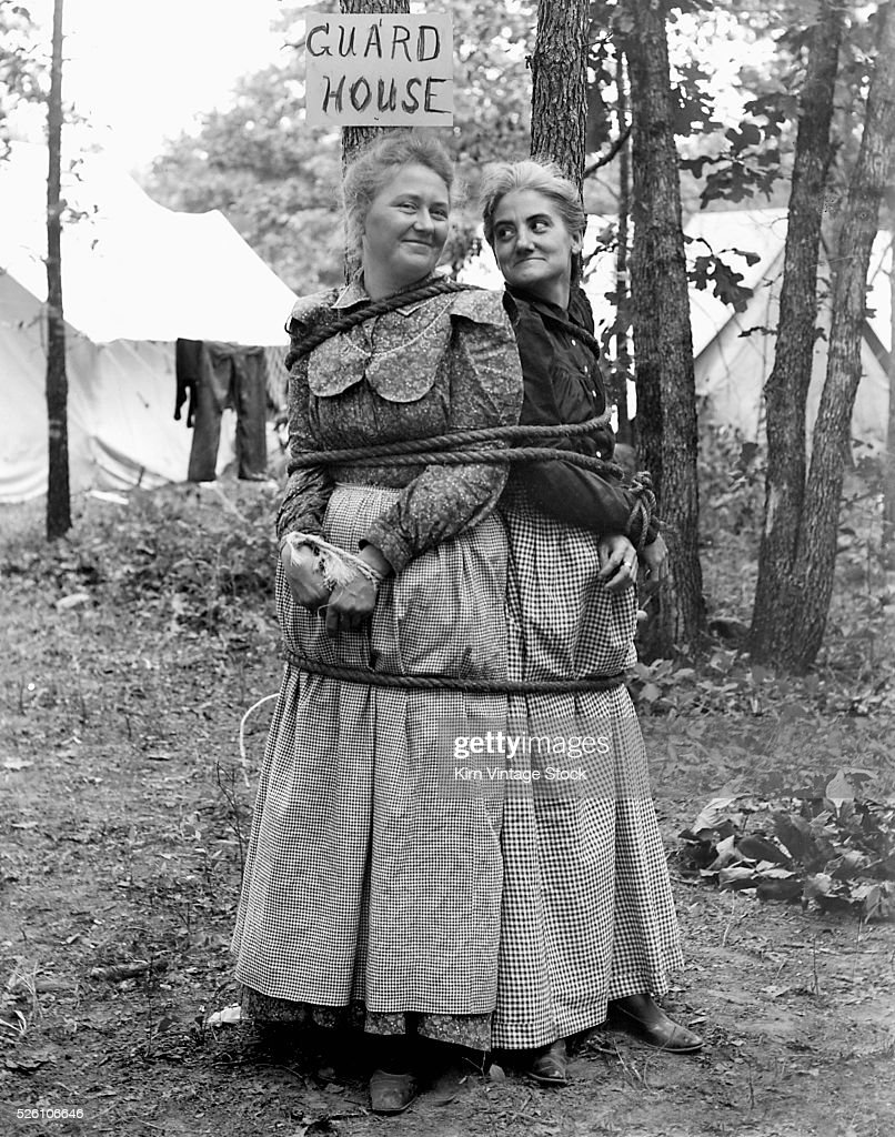 Two mature women are tied up to a tree on a camping trip ca 1905