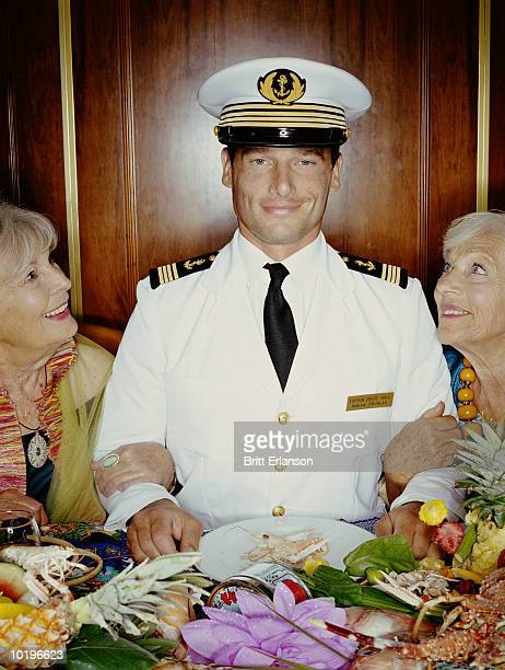 Two mature women arm in arm with captain at table, smiling, portrait
