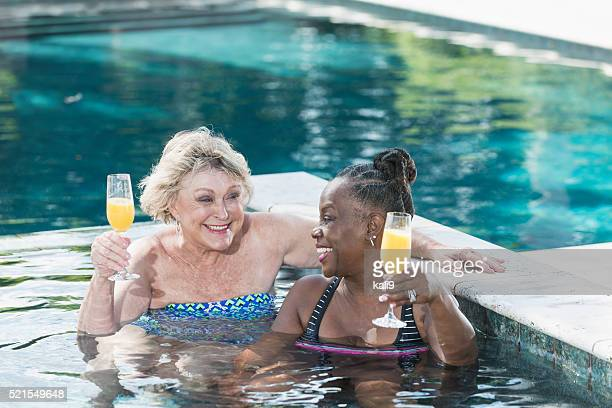 Two mature women enjoying cocktail in swimming pool