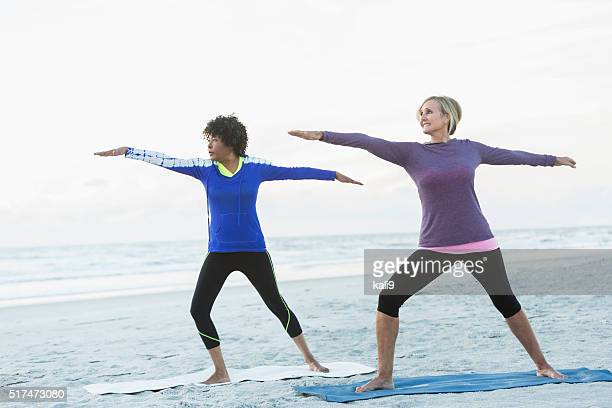 Two mature women exercising on beach