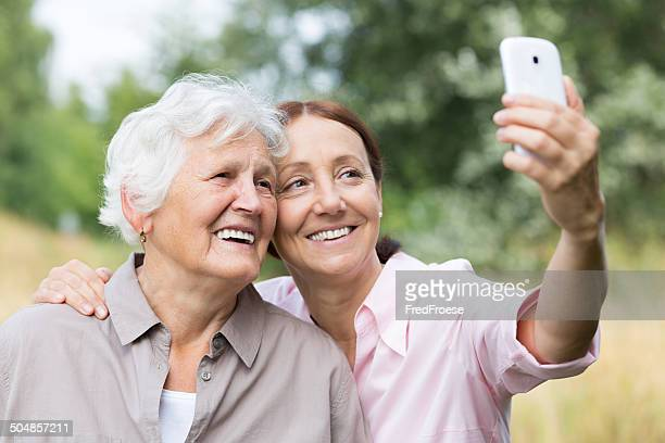 Two mature women outdoors taking selfie with mobile phone