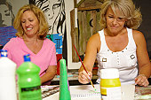Two mature women painting in art classroom