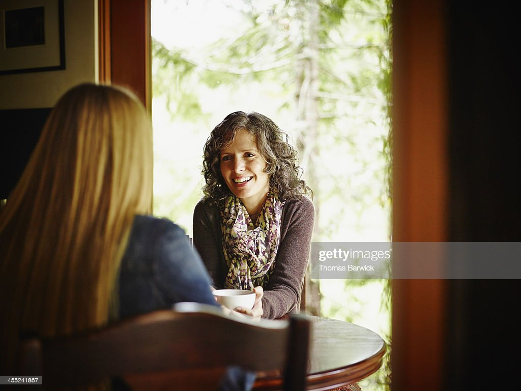 Two mature women sitting at kitchen table in cabin