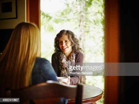 Two mature women sitting at kitchen table in cabin : Stock Photo